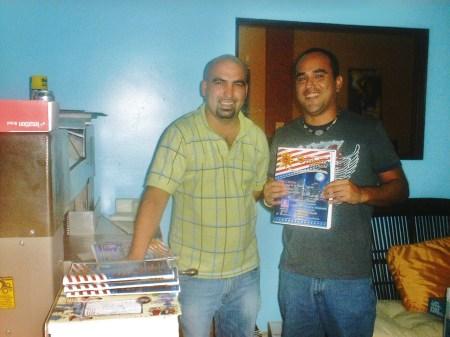 El diseñador de la Revista BRUJULAR DE MIAMI, César Venegas, y el Administrador, Kyustin Abreu, mostrando un número de la Revista.
