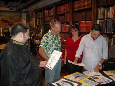 Los asistentes observando la muestra. En la foto, Leyser Martínez, junto a su esposa, la bloguera Niurki Palomino, preparando su grupo de caricaturas, mientras Raúl Ortiz y Josán Caballero se deleitan con ellas.
