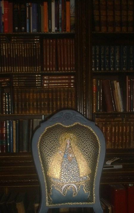 La maganífica estantería de la biblioteca del Centro de Arte CUBA 8, junto al mobiliario y la muestra de cuadros, cuyo centro es la Virgen de la Caridad del Cobre, nuestra Ochún. Mírela en el increible tapiz de esta silla.