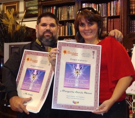 Niurki Palomino recibiendo de manos de Josán Caballero los Premios de Excelencia otorgados a la amiga Margarita García Alonso, poeta y bloguera de varios sitios webs destacados, colaboradora de la Revista BRUJULAR DE MIAMI.