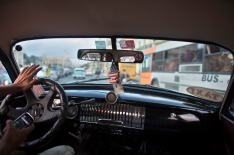 Taxi driver drives a vintage car in downtown Havana