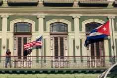 Un hombre en un balcón con las banderas de Estados Unidos y Cuba en La Havana