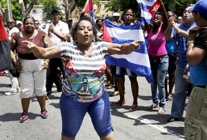 """Supporters of the Cuban government shout slogans against the """"Ladies in White"""", an opposition group in Havana September 13, 2015. Cuban authorities detained about 50 dissidents in Havana on Sunday when they attempted to march down a street in the capital a week ahead of Pope Francis' visit to the Communist-run country. Most of those arrested were members of the human rights group Ladies in White who for years, dressed in white and carrying pink gladiolas, have staged a weekly march along 5th avenue in the upscale district of Miramar after attending Mass, then rallied in a nearby park to denounce government repression. The organization is one of the few dissident groups in Cuba which has opposed the reestablishment of relations with the United States and is critical of the Roman Catholic Church's role in detent and support for cautious reforms undertaken by Cuban President Raul Castro. REUTERS/Enrique de la Osa - RTSWN3"""